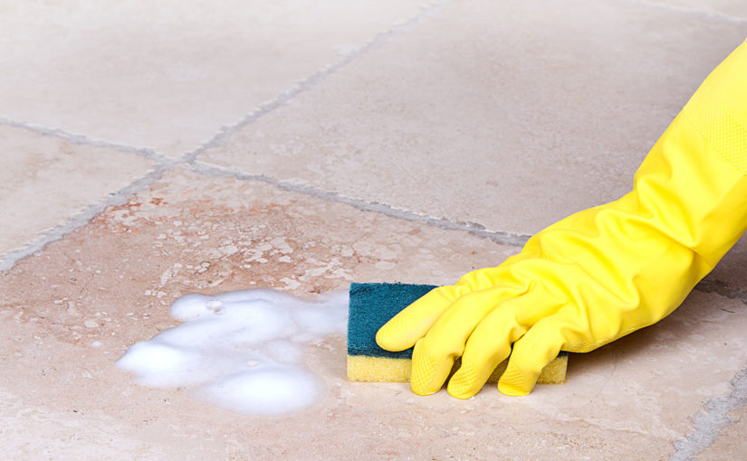 Hand wearing rubber glove cleaning basement tile with a sponge and soap.