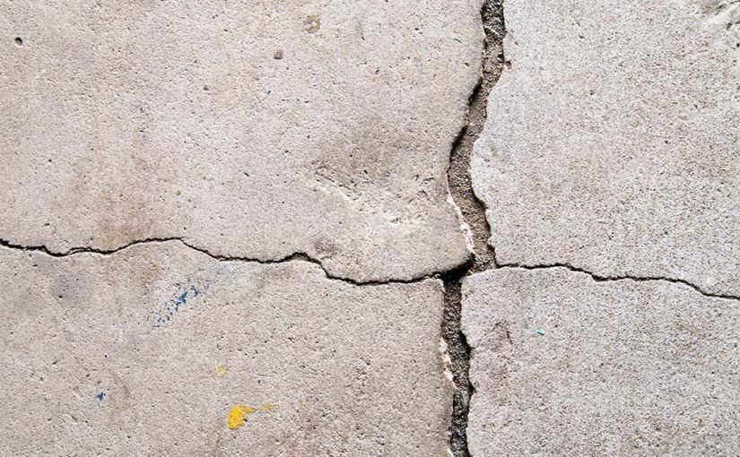Visible cracks in basement floor concrete.