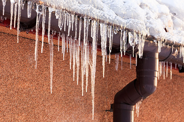 Gutters and downspout clogged with snow, creating an ice dam