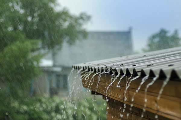 A roof draining water in a rain storm