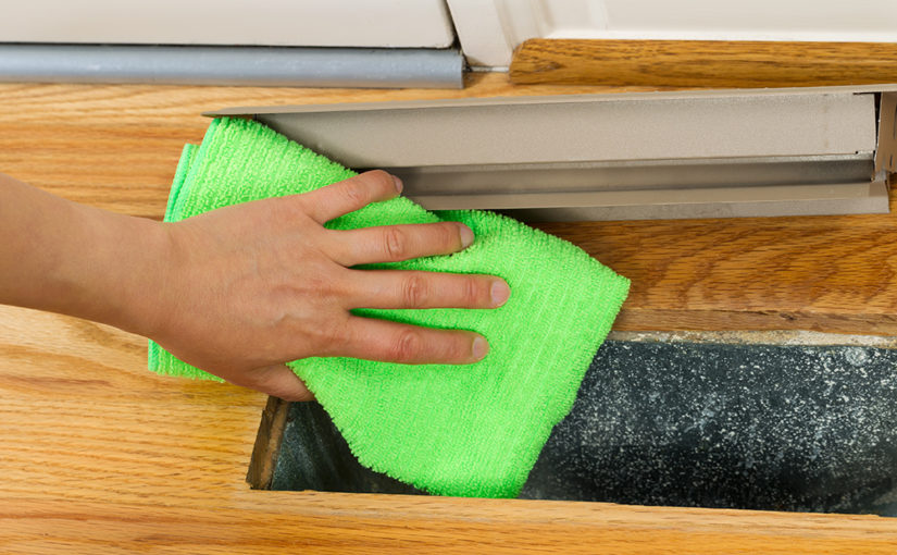 A floor vent is removed and cloth is used to dust it and the opening to improve indoor air quality
