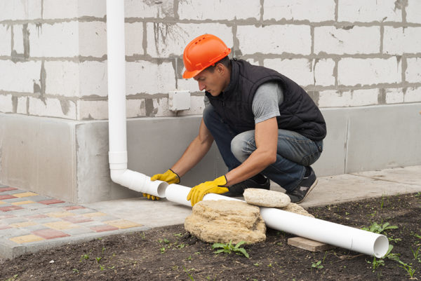 Construction worker installs pipe gutter system.